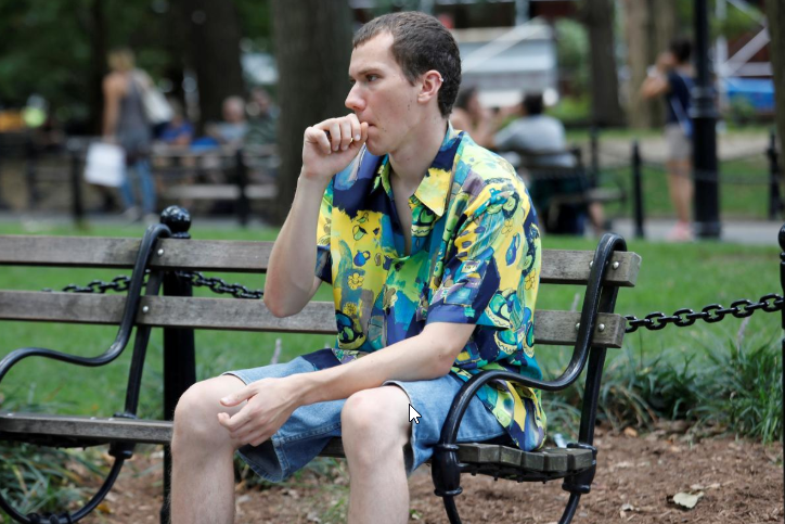 FILE PHOTO: Adam Trubitt, 21, vapes a Juul e-cigarette in Washington Square Park, Manhattan, New York, U.S., August 30, 2018. Picture taken August 30, 2018. To match Special Report VAPING-REGULATION/JUUL REUTERS/Shannon Stapleton - RC1693D4A300/File Photo
